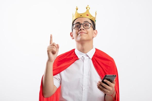 コピースペースで白い背景に分離された携帯電話を指して見上げるカメラを見て眼鏡をかけている赤いマントの若いスーパーヒーローの少年を喜ばせる