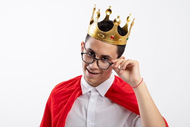Pleased young superhero boy in red cape wearing glasses and crown grabbing glasses looking at camera isolated on white background