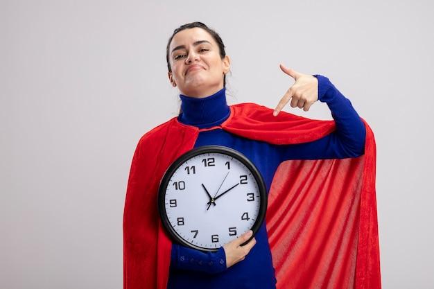 Довольный молодой супергерой девушка держит и указывает на настенные часы, изолированные на белом фоне