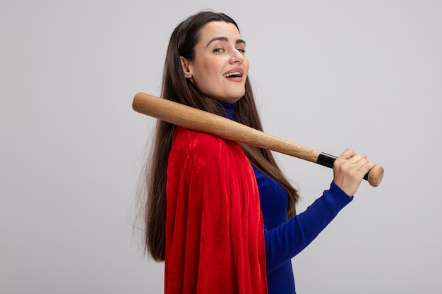 Pleased young superhero girl standing in profile view putting baseball bat on shoulder isolated on white background