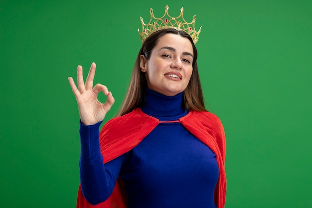 Pleased young superhero girl wearing crown showing okay gesture isolated on green