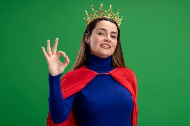 緑で隔離の大丈夫ジェスチャーを示す王冠を身に着けている若いスーパーヒーローの女の子を喜ばせる