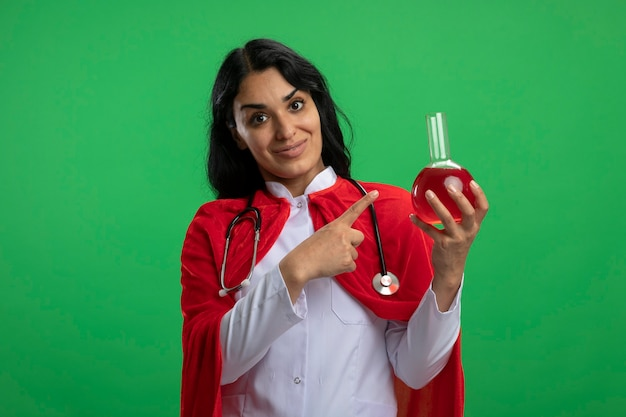 Lieta giovane ragazza del supereroe che indossa una veste medica con lo stetoscopio che tiene e indica la bottiglia di vetro di chimica riempita di liquido rosso isolato su verde