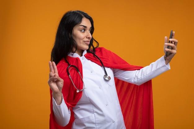 Довольная молодая девушка-супергерой в медицинском халате со стетоскопом делает селфи и показывает жест мира, изолированные на оранжевой стене