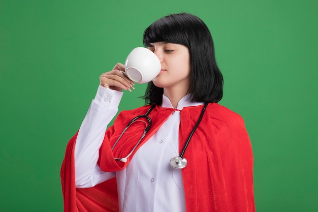 Pleased young superhero girl wearing stethoscope with medical robe and cloak drinks tea isolated on green wall
