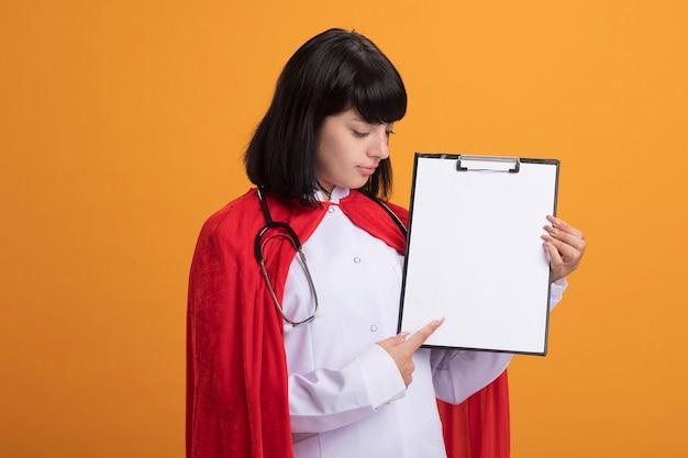 Felice giovane ragazza del supereroe che indossa uno stetoscopio con abito medico e mantello che tiene e punti negli appunti isolati sulla parete arancione