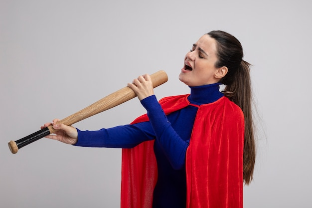 Pleased young superhero girl with closed eyes holding baseball bat and sings isolated on white background