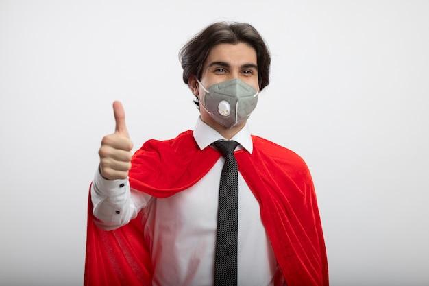 ネクタイと白い背景で隔離の親指を示す医療マスクを身に着けているカメラを見て喜んで若いスーパーヒーローの男
