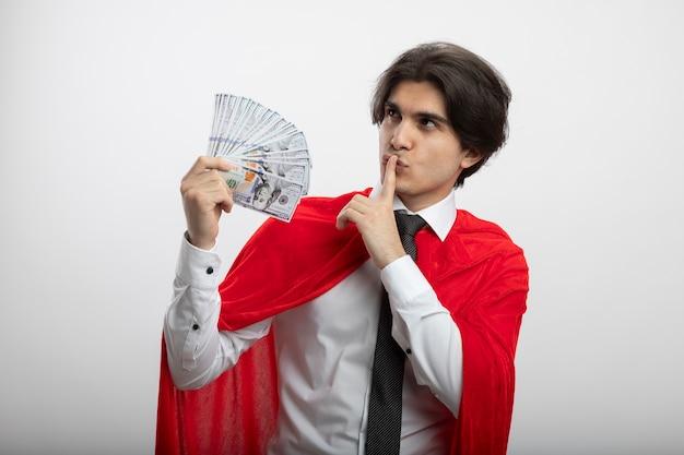 현금을 들고 침묵 제스처를 보여주는 넥타이 착용 측면을보고 기쁘게 젊은 슈퍼 히어로 남자