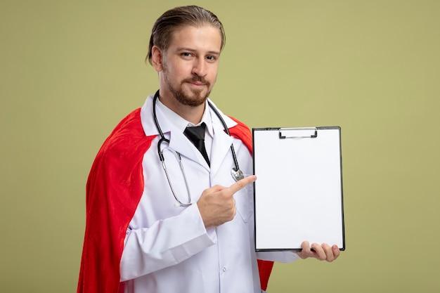 Довольный молодой супергерой, носящий стетоскоп с медицинским халатом и указывая на буфер обмена, изолированный на оливково-зеленом фоне