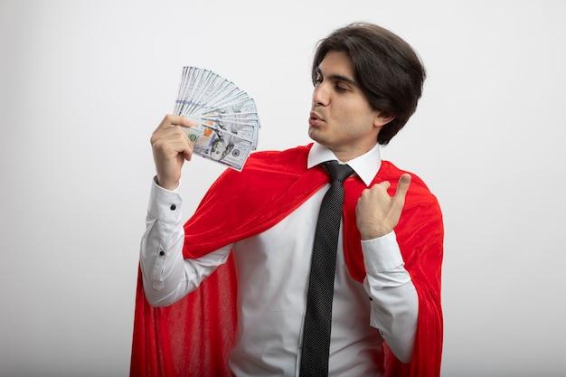 ネクタイを保持し、白い背景で隔離の現金を見て喜んで若いスーパーヒーローの男