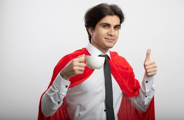 お茶のカップを保持し、白で隔離の親指を見せてネクタイを身に着けている若いスーパーヒーローの男を喜ばせる