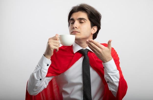 Felice giovane supereroe ragazzo con gli occhi chiusi che indossa cravatta annusando caffè isolato su bianco