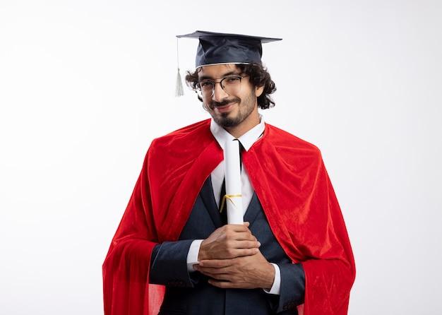 赤いマントと卒業帽のスーツを着て光学メガネで満足している若いスーパーヒーローの男は卒業証書を保持し、白い壁に隔離された正面を見る