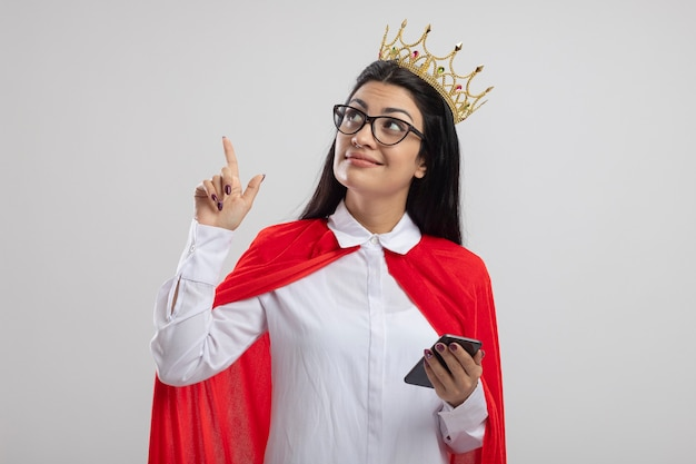 Felice giovane superdonna con gli occhiali e corona che tiene il telefono cellulare alla ricerca e rivolto verso l'alto isolato sul muro bianco