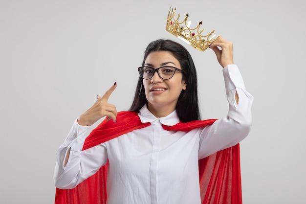 Lieta giovane superdonna con gli occhiali che tiene la corona sopra la testa guardando la parte anteriore rivolta verso la corona isolata sul muro bianco