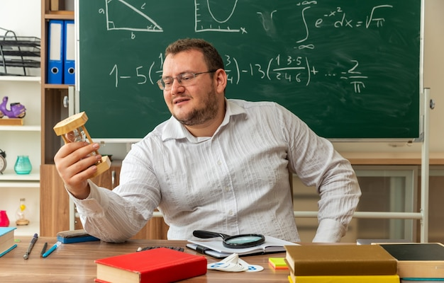 Pleased young teacher wearing glasses sitting at desk with school supplies in classroom keeping hand on waist holding and looking at hourglass