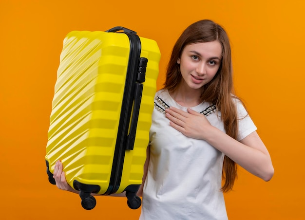 Довольная молодая путешественница держит чемодан и кладет руку на сундук на изолированном оранжевом пространстве
