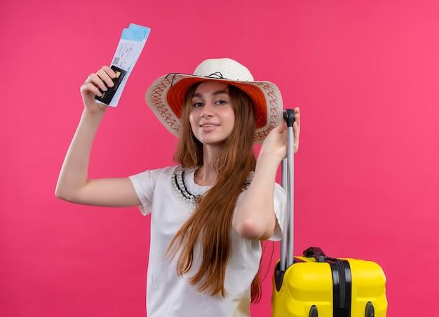 Довольная молодая путешественница в шляпе держит кредитную карту, билеты на самолет и чемодан на изолированном розовом пространстве