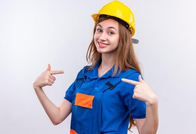 建設制服と安全ヘルメットで若い女性ビルダー労働者が自分自身に指を指して、誇りを感じて喜んでいます
