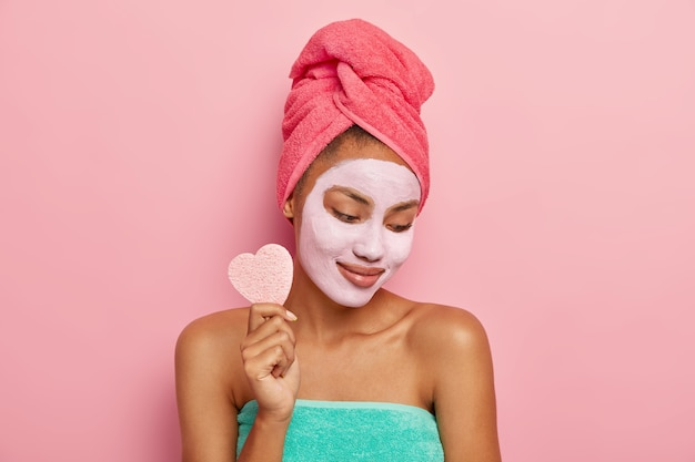 Pleased young woman focused down, applies facial clay mask, holds cosmetic sponge for removing makeup, shows bare shoulders, wrapped in bath towel, isolated on pink studio wall