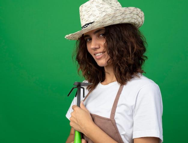 녹색에 고립 된 괭이 갈퀴를 들고 원예 모자를 쓰고 제복을 입은 기쁘게 젊은 여자 정원사