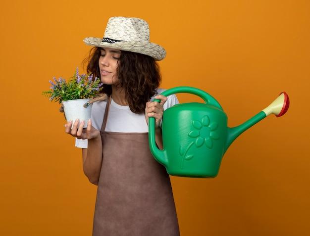 オレンジ色のじょうろを保持しているガーデニング帽子を身に着けている制服を着た若い女性の庭師を喜ばせる