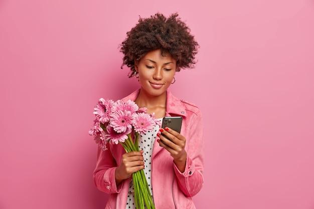 La giovane donna soddisfatta ha i capelli afro, ha un bouquet di gerbera come regalo, posa con bellissimi fiori e smartphone in mano, invia messaggi online, riceve un regalo a sorpresa