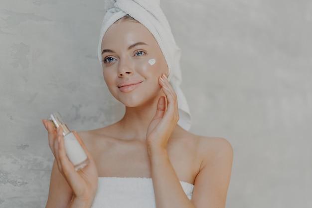 Довольная молодая женщина имеет здоровую сияющую кожу, минимальный макияж, наносит лосьон для лица и радостно смотрит вдаль, носит обернутое полотенце на голове и вокруг тела, позирует у серой стены.