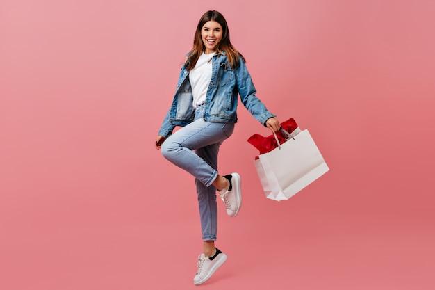 店のバッグを持って喜んでいる若い女性。デニムの服装で魅力的なヨーロッパの女の子の完全な長さのビュー。