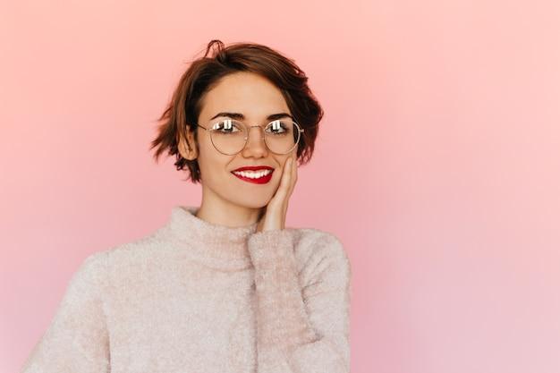 顔に触れる眼鏡の若い女性を喜ばせる