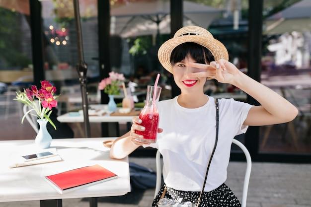 夏の朝に冷たい飲み物のガラスを保持し、ピースサインでポーズをとって麦わら帽子の若い女性を喜ばせる