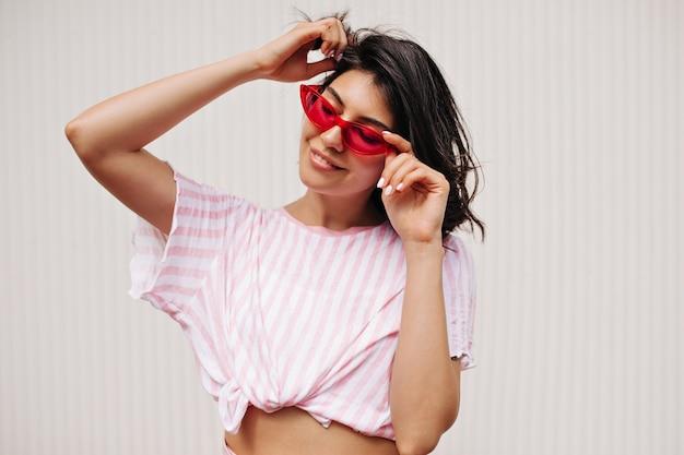 テクスチャ背景に分離された若い女性を喜ばせます。笑顔でポーズをとるピンクのサングラスの愛らしい女性。