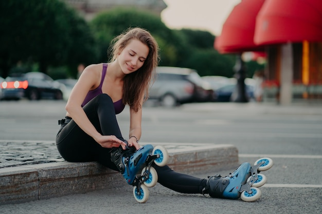 Pleased young woman puts on rollerskates going to ride rolles in urban place has regular exercising goes in for dangerous sport adjustes laces
