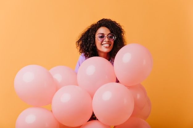 Lieta giovane donna in occhiali rotondi in posa con palloncini rosa. gioiosa ragazza di compleanno africano isolato su giallo.
