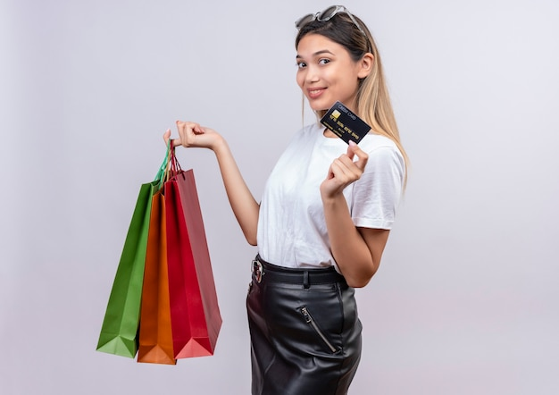 A pleased young woman in white t-shirt wearing sunglasses on her head showing credit card while holding shopping bags on a white wall
