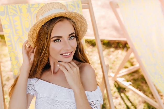 喜びで夏を過ごす庭で長椅子でリラックスする驚くべき緑色の目を持つ満足している若い女性。手で顔を支え、笑顔の帽子をかぶった嬉しい女の子のクローズアップの肖像画。