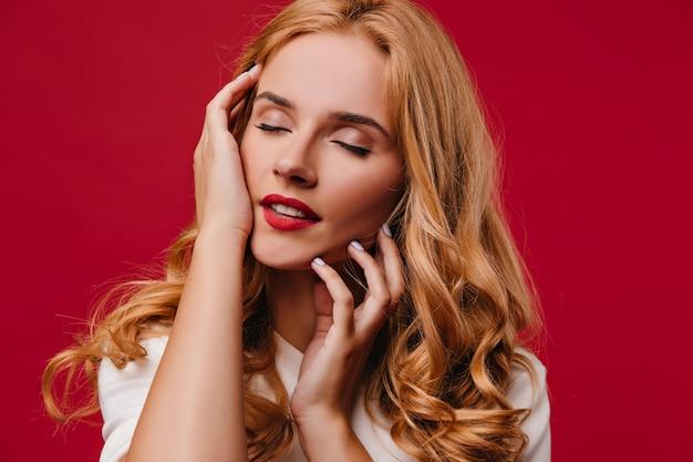 目を閉じてポーズをとるブロンドの髪を持つ若い女性を喜ばせます。赤い壁に立っているのんきな金髪の女の子。