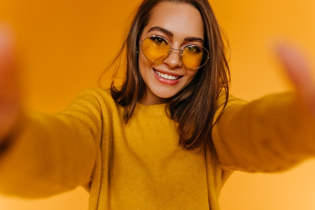 Довольная молодая женщина с каштановыми волосами делает селфи на желтой стене с очаровательной улыбкой. привлекательная девушка фотографирует себя и смеется.