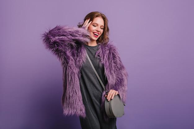 Lieta giovane donna con elegante borsetta in posa con gli occhi chiusi su sfondo viola