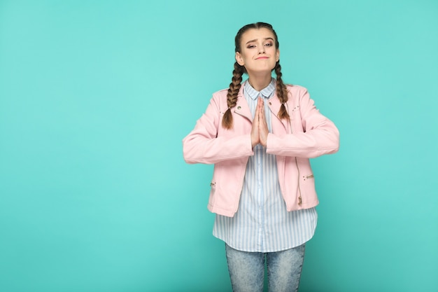 Pleassed asking portrait of beautiful cute girl standing with makeup and brown pigtail hairstyle in striped light blue shirt pink jacket. indoor, studio shot isolated on blue or green background.