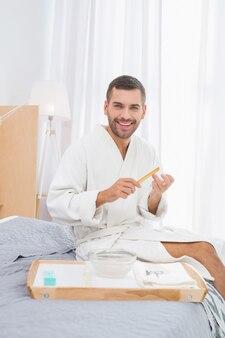즐거운 시간. 집에서 쉬고있는 동안 그의 손톱을 정리하는 기쁘게 좋은 남자
