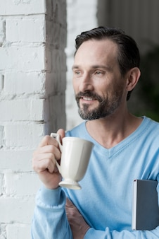 Pleasurable time. delighted optimistic bearded man holding a notebook and smiling while enjoying his coffee