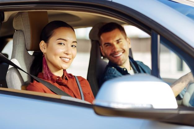 楽しい旅。彼氏と車で旅行しながらあなたを見ている素敵な陽気な女性