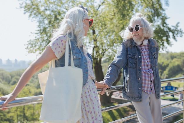 즐거운 산책. 서로를 보면서 다리에 서있는 좋은 노인