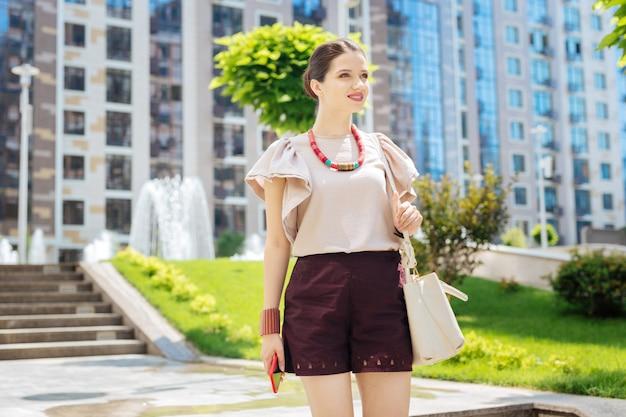 楽しい週末。街を散歩しながら彼女のバッグを保持している喜んでいる若い女性