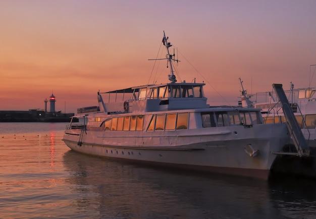 Прогулочные катера у пристани в ялте ранним утром ярко-розовые в ясном небе