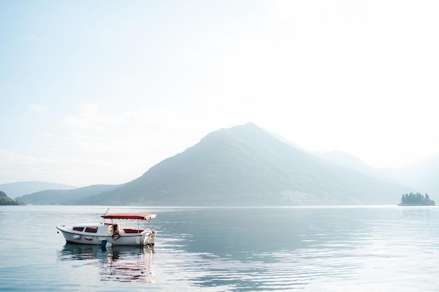 霧の中の山々を背景に赤い太陽が降り注ぐ白いモーターボート。
