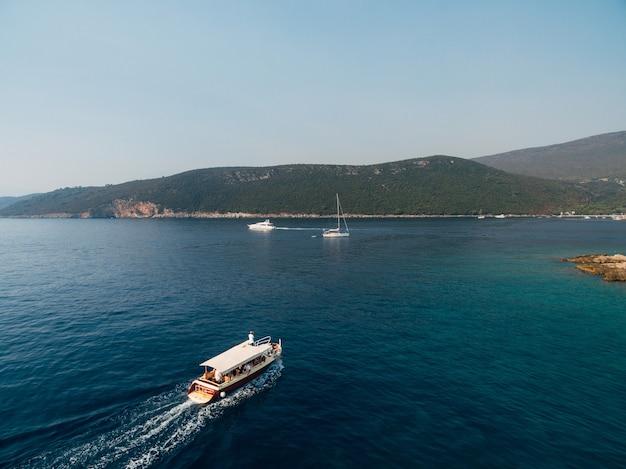 Белая прогулочная яхта с навесом и людьми на борту плывет по морю к берегу.