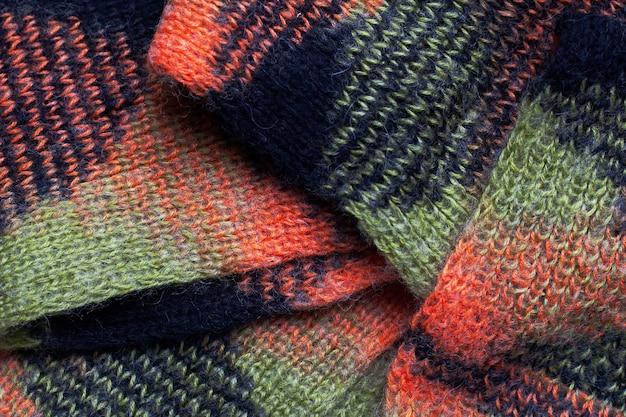生地のプリーツ、オレンジブラックグリーンのニット素材、スカーフの折り目。